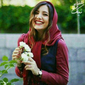 دختر زیبای ایرانی با لباس قرمز و گل سفید در دست